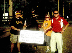 O.A.T.S. rider Grant and mom Kelly Harned present a check to O.A.T.S. from the Enterprise Holdings Foundation.
